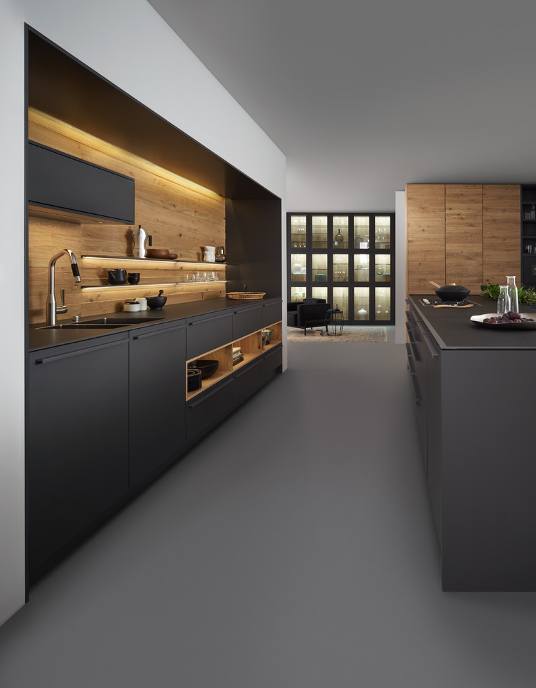 modern kitchen set in wood and charcoal tones single but large kitchen island with flat panel cabinets and double bowl shaped sinks charcoal toned floors wood backsplash black countertop
