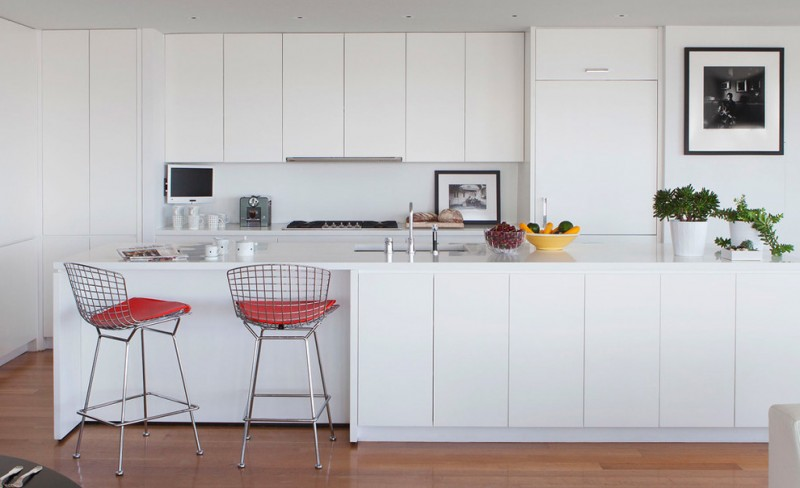 modern minimalist kitchen in white i shaped countertop white cabinets clean and compact kitchen island with storage a pair of light steel stools with red comforters