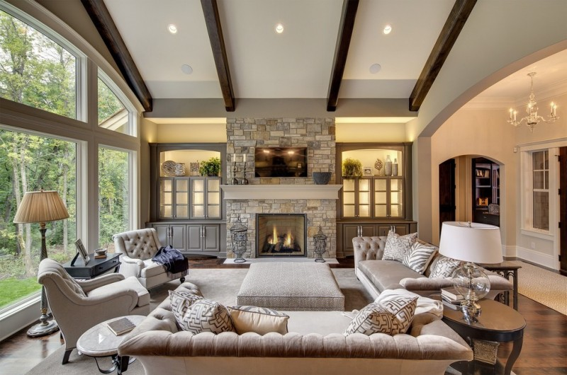 morning room furniture beige sofa round tables foot rest standing lamp ceiling lights chandelier stone fireplace hardwood floors white walls transitional design