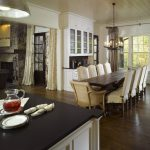 narrow dining room tables hardwood floors windows kitchen island oven chandelier floor to ceiling cabinets drawers tall back chairs traditional design