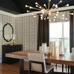 Narrow Dining Room Tables Low Back Chairs Modern Chandelier Mirror Geometrical Pattern Wallpaper Hardwood Floors Wooden Cabinets Oversized Windows Transitional Design