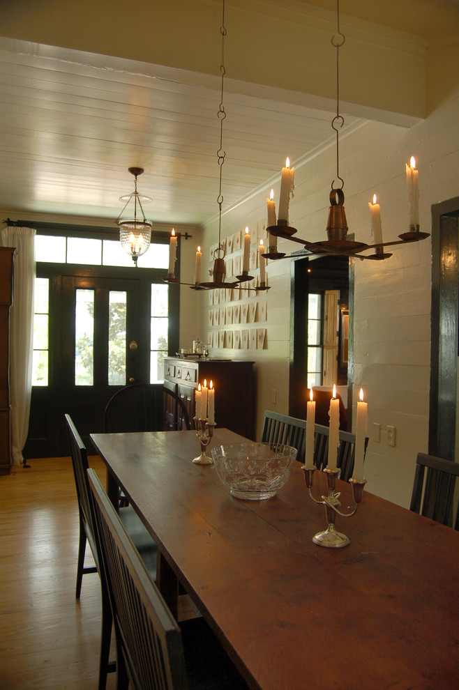 narrow dining room tables tall back benches hanging candleholders candles hardwood floor glass vase beige walls farmhouse design