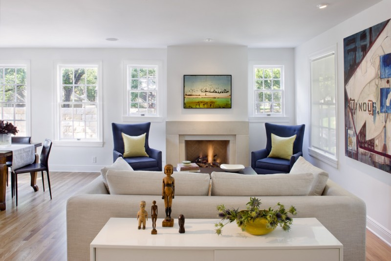 navy blue armchairs with light yellow accent pillows light yellow cushion white back table medium toned wood floors white modern fireplace