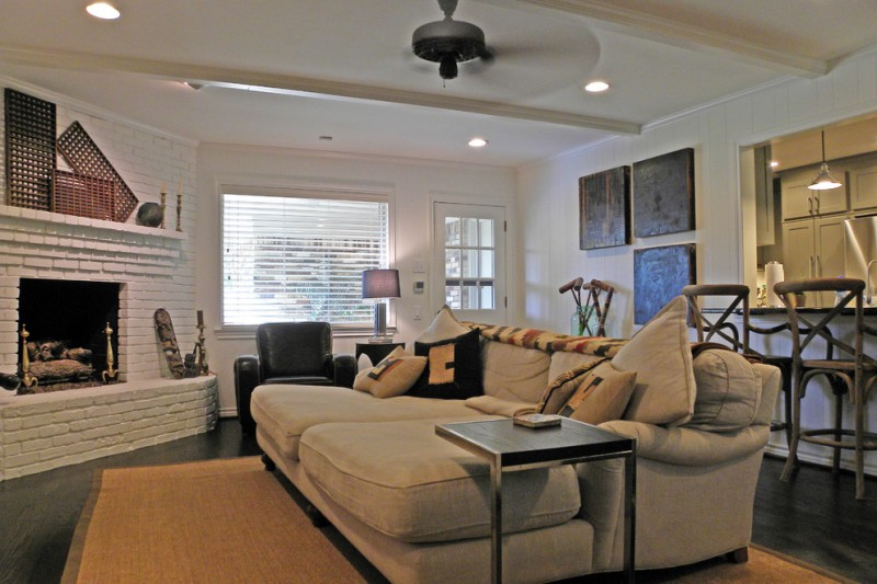oversized couches living room brick fireplace ceiling fan lights hardwood floors small table kitchen island tall back chairs decorations pendant blinds rugs eclectic design