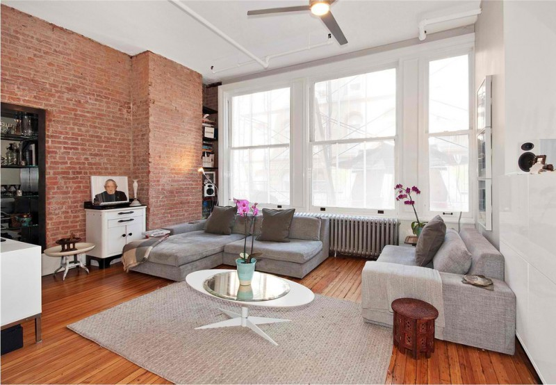 oversized couches living room brick wall round tables decorations white cabinets blackened steel book shelf hardwood floors rug liht fixtures modern design