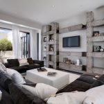 oversized couches living room column shape shelves wall mounted tv white ottoman table ceiling lights window walls screen panel glass door modern design