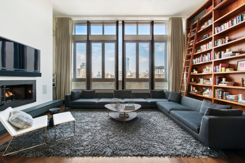 oversized couches living room floor to ceiling bookshelves wall mounted tv chaise longue foot rest small table rug throw pillows hardwood floors tall windows contemporary design