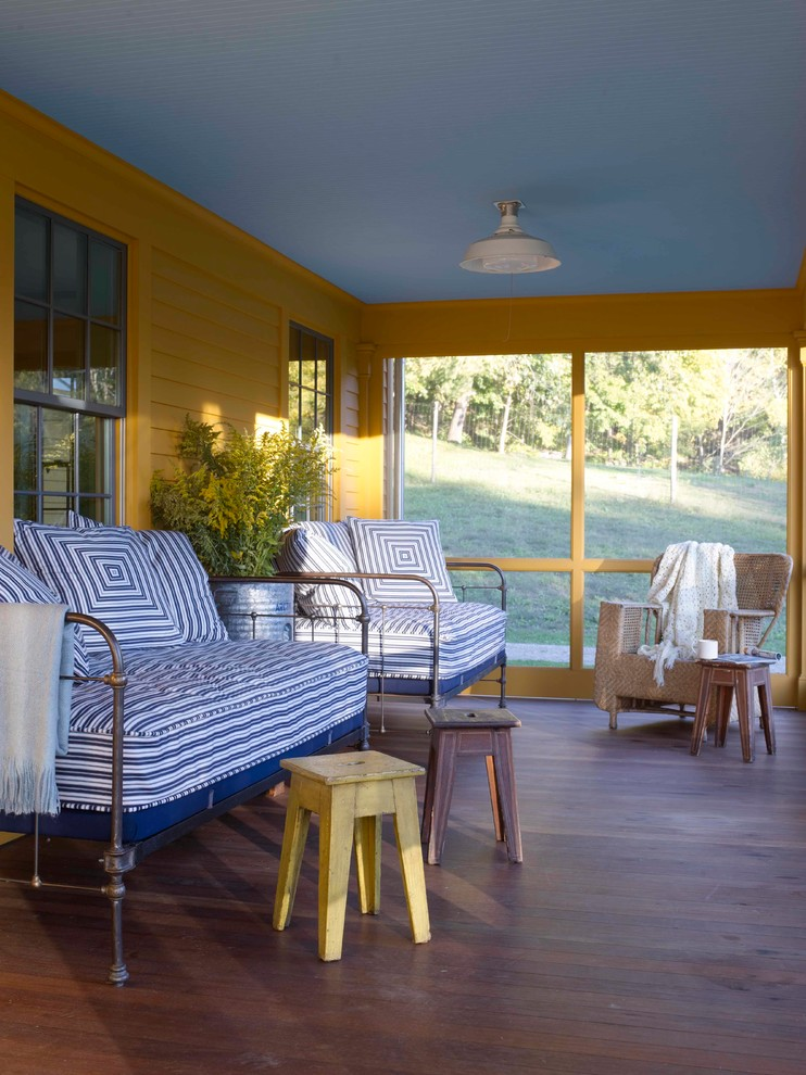 oversized couches living room stools hardwood floors glass panel windows pendant yellow walls blue ceiling farmhouse design