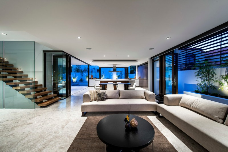 oversized couches living room tables stairs glass panels ceiling lights marble floors brown rugs island chairs kitchenette contemporary design