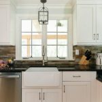 pedestal sink with backsplash wall cabinets drawers kitchen utensils marble countertop slate stove traditional style