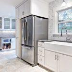 pedestal sink with backsplash wall cabinets shelves window countertop fridge marble tile hanging lamp contemporary design