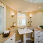 pedestal sink with backsplash wall lamps ceiling lights drawers cabinets stone floor towel rack traditional design