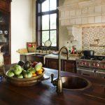 pedestal sink with backsplash wooden countertop kitchen island display rack stove utensils urn faucet rustic style