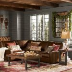 Pottery Barn Sectional Leather Sofa Grey Painted Wooden Deck Wall Leather Pillow Throws Wooden Coffee Table Table Lamp Wooden Ceiling Red Rug