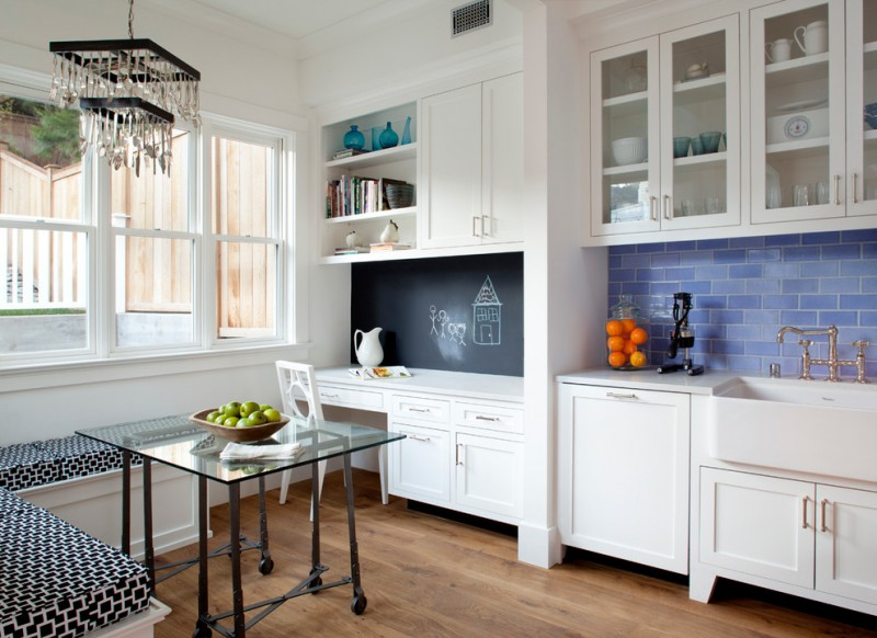 rectangular glass table board wall white cabinet white chair light toned wooden floors white wall ceiling pendant lamp blue backsplash