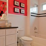 Red White Walls With Black Lines White Corner Bathtub White Toilet Bathroom Vanity With Black Top And White Cabinets And White Framed Mirror White Ceramic Floors With Black Accent