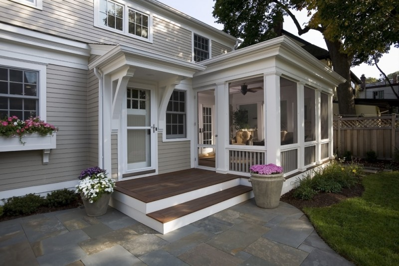 screen porch designs urns decking wood steps stone pavers garden patio upholstered chairs grey walls wood fence white pillars traditional design