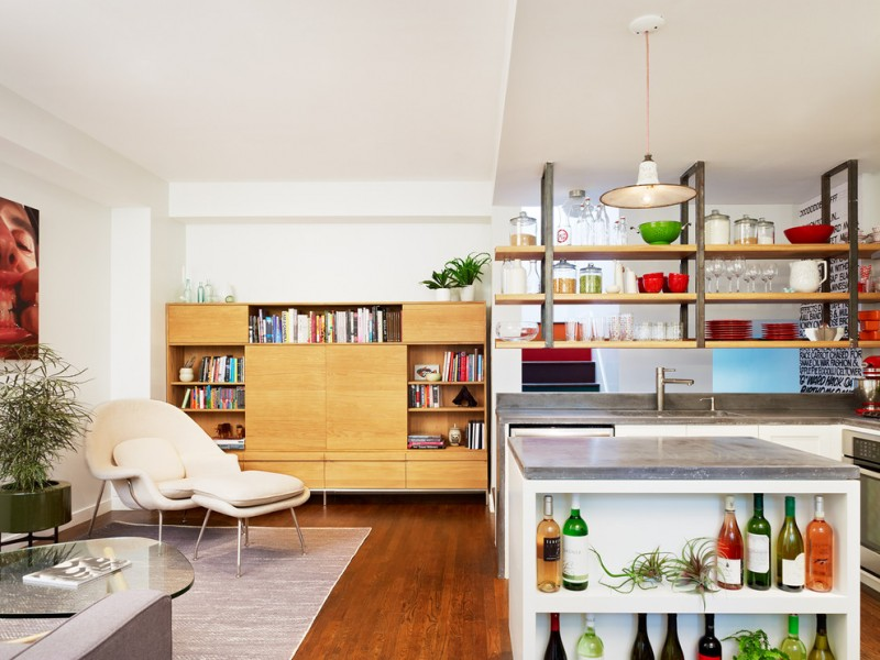 simple modern kitchen island with metal top and side wine open shelves in white darker hardwood floors modern reclining chair in white retro style book rack made of wood