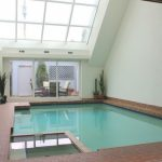 Slanted Glass Pool Enclosure Idea Dark Brown Tiles Floorings White Painted Walls Some Decorative Plants With Their Burnt Clay Pots