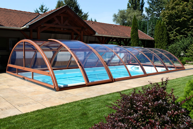 small and practical un ground pool enclosure idea made of glass and supported by aluminum