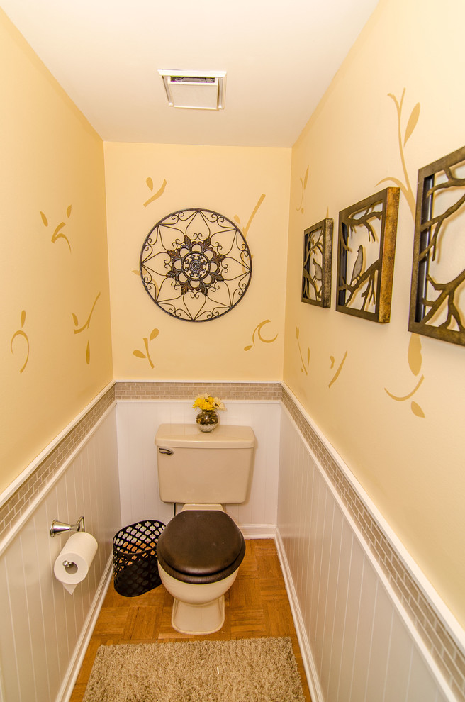 small bathroom with wall arts two piece toilet beige concrete walls white subway ceramic tiles walls wood floors fluffy mat
