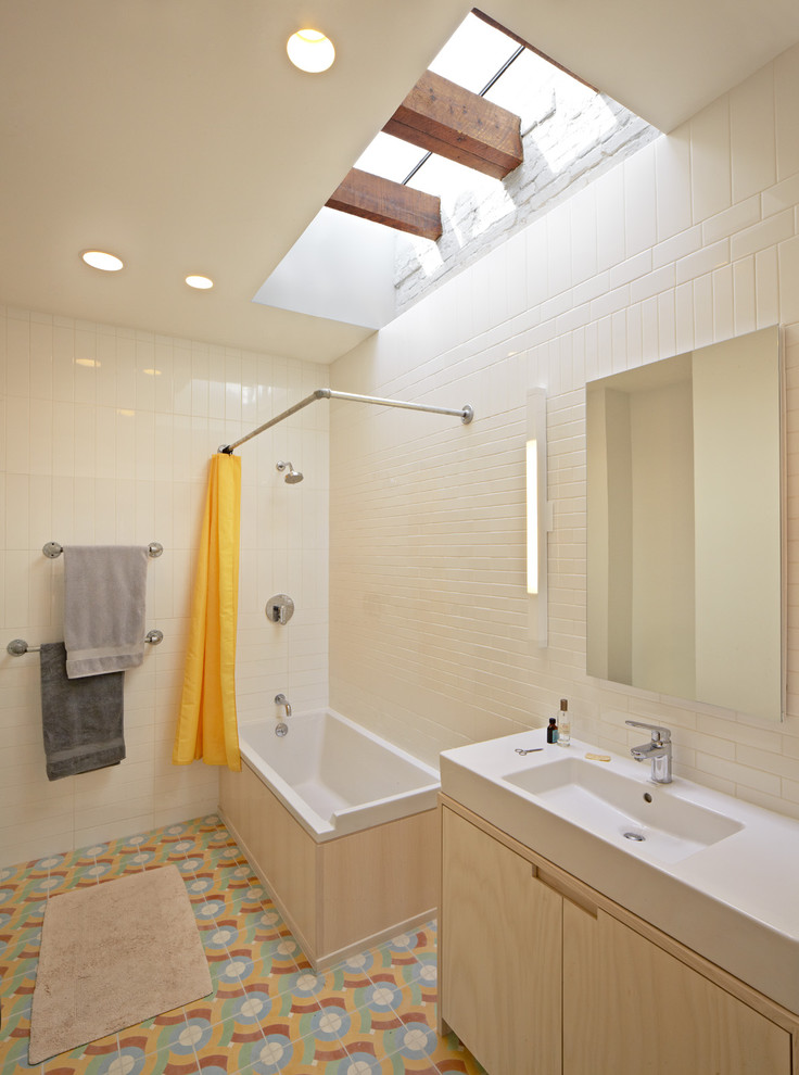 small bathtub with shower orange curtain towels towel racks faucets modern lamp ceiling lights mirror vanity eclectic bathroom
