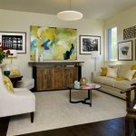 Soft Beige Walls Light Yellow Hand Painting Classic Wood Console Table Light Cream Cushions With Bright Yellow Accent Pillows Cream Area Rug Dark Toned Wood Floors
