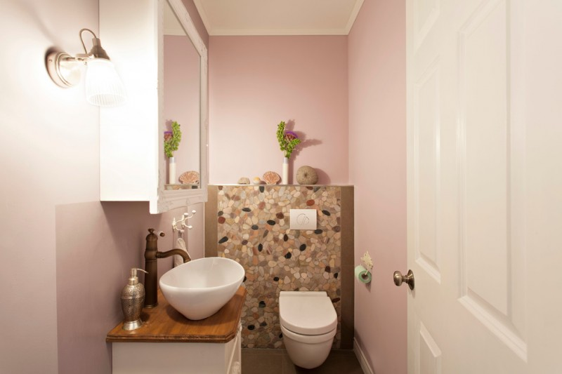 soft pink walls with stone wall decoration wall mounted toilet small size bathroom vanity with wood countertop white framed mirror with hidden storage white sink