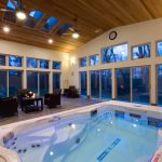 Spa Pool & Swimming Pool With Clear Finishing Cedar Enclosure A Set Of Black Furniture Light Beige Walls With Frameless Glass Windows And Door