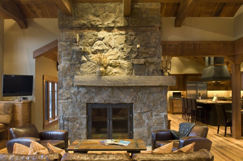 stone fireplace wall leather sofa wooden table wooden floor wooden ceiling dining room stainless steel appliances metal hood