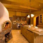 Stone Wall Fireplace Chimney Log Storage Tiled Floor Kitchen Island Ceiling Beams Granite Backspace Granite Countertop Arcway