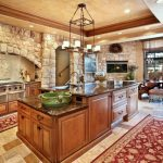 Stone Wall Light Stone Floor Area Rug Wooden Kitchen Island Granite Countertop Hanging Lights Archway Stainless Steel Appliances
