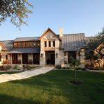 texas ranch house plans gable roof chimneys stone walls pavers patio round chairs trees rustic design