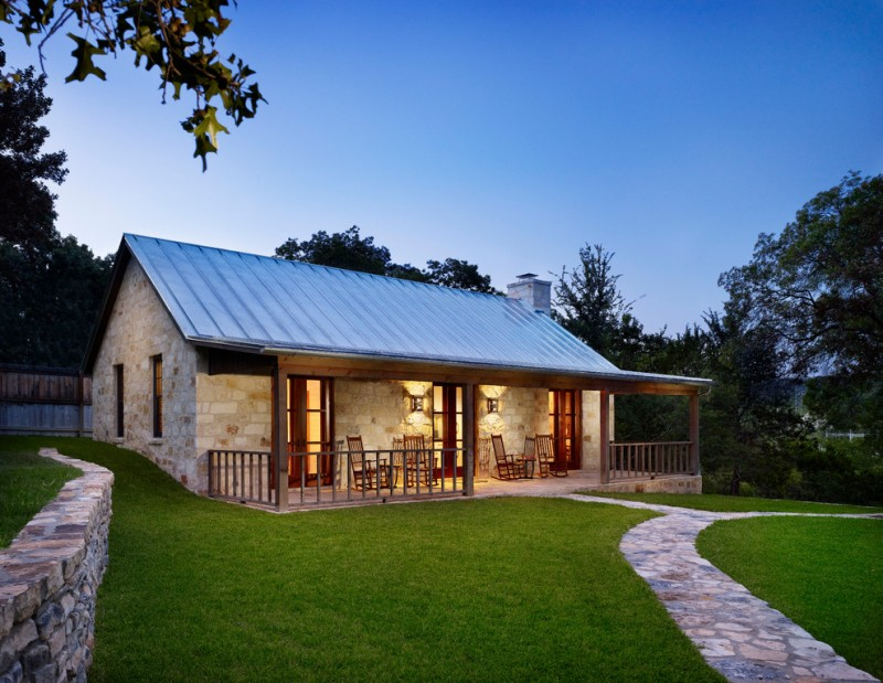 texas ranch house plans stone exterior wood pillars fence patio tall back chairs light fixtures pavers grass farmhouse design