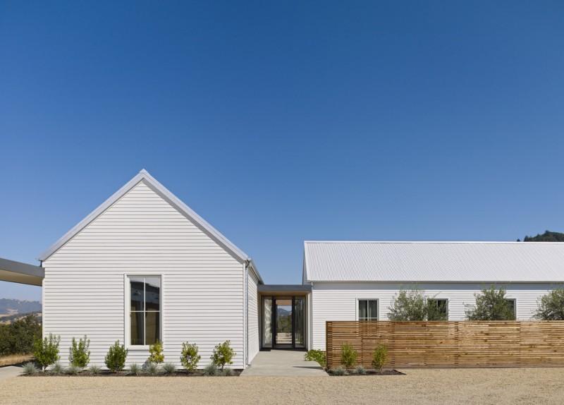 texas ranch house plans white exterior wood fence column windows stone pavers glass door decorative plants farmhouse design