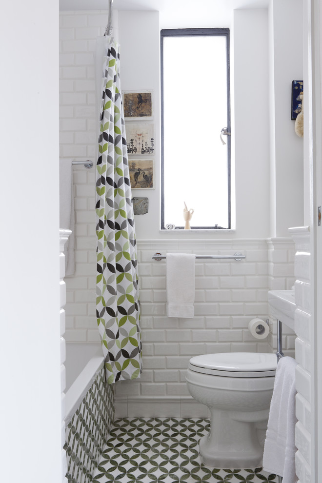 tiny bathroom with concrete and bricks walls in white wall mounted toilet in white white bathtub with pattern on its walls multicolored shower curtain multicolored ceramic floors