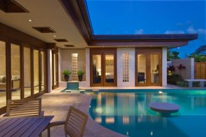 travertine pavers pool deck double glass doors ceiling lights wood table armchairs fountain white bench decorative plants contemporary design