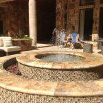 travertine pavers pool deck fountain medium back chairs stone table stool patio decorative plants traditional design