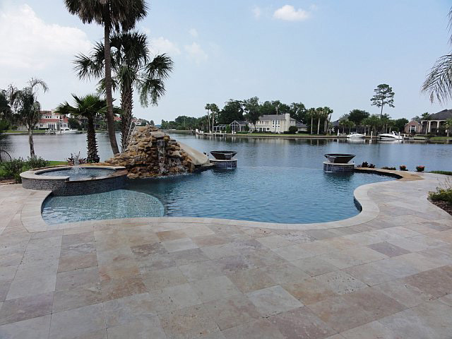 travertine pavers pool deck fountains hot tub stone walls plant pots patio tropical style