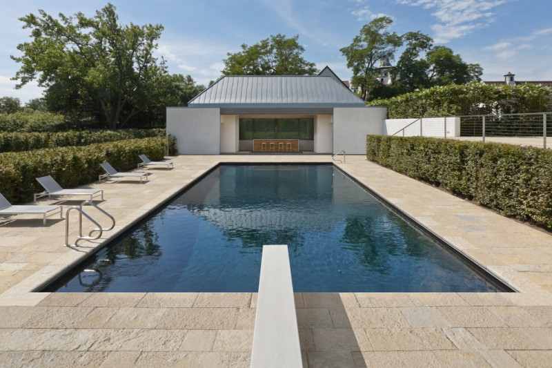 travertine pavers pool deck loungers bush walls fence house stools blue roofs modern design
