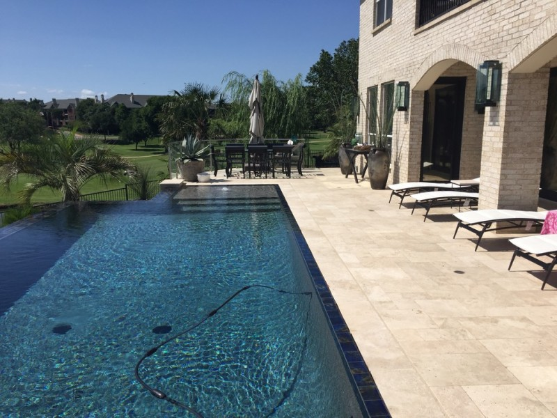 travertine pavers pool deck loungers wall lamps stone tiles patio low back chairs round table trees decorative plants traditional design