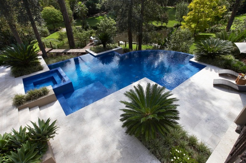 travertine pavers pool deck lounges small wood table sunbrella fence trees decorative plants contemporary design