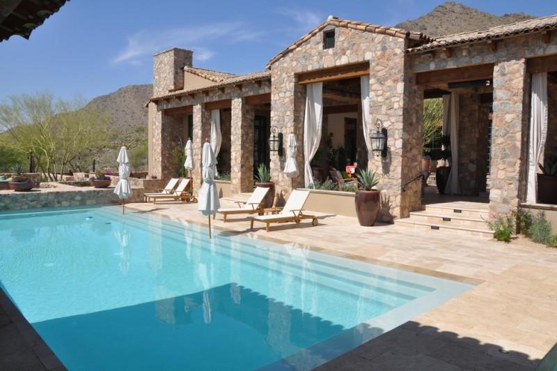 travertine pavers pool deck lounges sunbrella hanging lamps stone walls curtains decorative plants mediterranean design