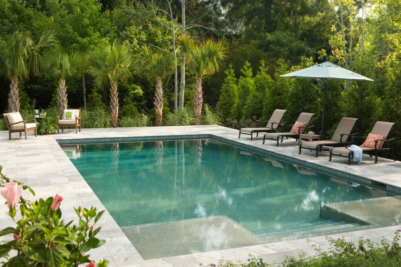 travertine pavers pool deck lounges sunbrella low back chairs throw pillows trees plants traditional design