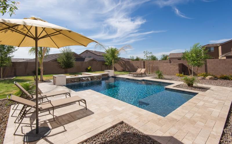 travertine pavers pool deck lounges sunbrella pebbles decorative plants fountain lawn contemporary design