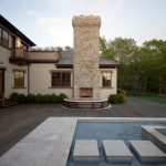 travertine pavers pool deck outdoor fireplace half round bench stone steps oversized windows double glass doors traditional design