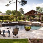 travertine pavers pool deck patio covers tall back chairs brick pillars wall lamps spa fountains traditional design