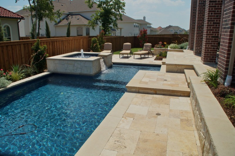 travertine pavers pool deck patio loungers hot tub fountain stone steps brick walls wood fence decorative plants traditional design