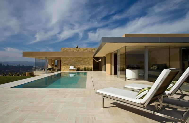 travertine pavers pool deck patio loungers throw pillows double glass doors oversized windows garden modern design