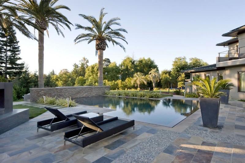 travertine pavers pool deck plant pots stone walls steps loungers garden patio trees decorative plants contemporary design